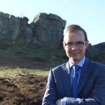 Photo of Ilkley candidate Kyle Green, standing in fromt of the famous Cow and Calf Rocks, Ilkley.